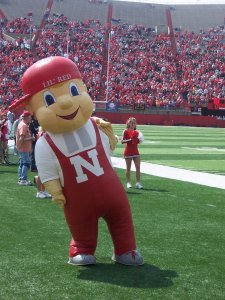 "Knowing he was too creepy for the restaurant business unlike his more successful cousin, Big Boy, Lil' Red traveled to Lincoln, Nebraska to be a mascot to the Cornhuskers. Still, he seems more appropriate for a mom-and-pop restaurant with a ""21 and over"" sign than a school sporting event."