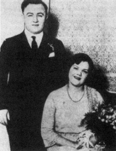 Dean O'Banion posing in a photo with his wife Viola holding one of his bouquets he styled himself. Too bad he'll be whacked by Frankie Yale's boys in his own flower shop.