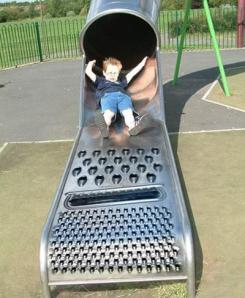This boy seems utterly scared for dear life landing on the cheese grating slide. Perhaps he didn't see where he'd land before going down the slide.
