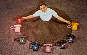Of course, you know that this postcard is vintage when you see rotary dial telephones in them. Still, this woman seems so happy that she wants them all despite none of them matching her dress.