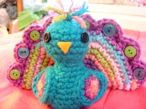 Even though this little peacock is a little girl's toy, it's very obvious this little crocheted stuffed animal is a boy. Seriously, peacocks don't lay eggs and are built with such a feathered train to attract peahens.