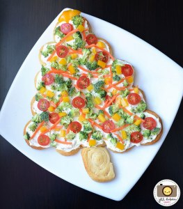 This is made from either bread or pizza dough spread over with cream cheese as well as topped with carrots, cherry tomatoes, yellow peppers, and broccoli. Still, it's a healthier option than the cheese candle wreath one. Yet, won't satisfy vegans.