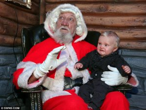 Let's just sum up what makes this Santa terrifying as hell: 1. The ugly wig you'd see on someone playing George Washington. 2. The beard you'd see on a homeless bum. 3. The red hood which doesn't go good on him. Still, I can see why this baby isn't a happy camper.