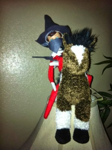 Either this elf on the shelf is an Old West bandit or some 18th century highwayman. Either way, you wouldn't want to mess with him.