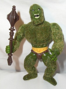 """Comes with his own club and speedo. And yes, he's supposed to be a bacteria grabbing walking carpet as if he was a lovechild between the Incredible Hulk and the Grinch. Also said to have """"a real pine scent."""" Creepy."""
