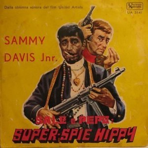 Hate to say this, but Sammy Davis Jr. looks totally like a gangster in this with his bling, leather jacket, smoking his cigarette, and wielding an AK-47 while Lawford seems asking for cash.