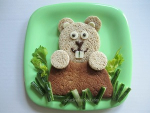 Okay, now the ground is made from a whole wheat tortilla while the groundhog is made from bread. The grass is of lettuce and cucumber. And the white stuff of cheese. Yet, I'm sure your child will love it since it's so cute.
