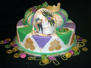 I do like the nice prop usage on this cake such as the mask, crown, Doubloons, and beads. Yet, I wonder if this cake is chocolate underneath the icing.