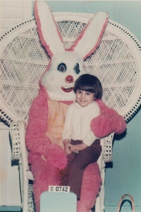 This girl sitting on his lap doesn't seem to be crying. Either she's very brave or really has no idea of what that bunny has in store for her.