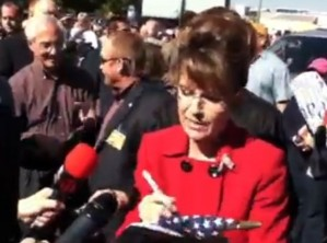 For a Vice Presidential candidate known for her extremely hateful conservative comments and love for traditional American values, Sarah Palin sure doesn't have any qualms about desecrating the American flag with her autograph.