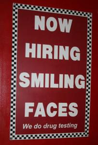 Yes, they want smiling faces but if you show up too happy, they may think you're high. Still, if this is for some minimum wage service job, I suppose happy drug free people will be hard to come by.
