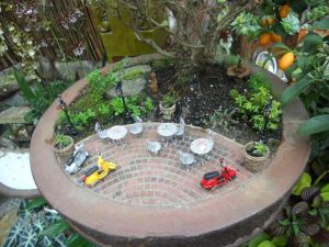 Now this is a miniature garden containing a small patio with scooters. Still, it's quite creative and probably made by someone with too much time on their hands.