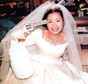 Sure she may be a blushing bride. But having her smile as she points a gun to her head, well, I have to wonder about her state of mind. I mean does she have a death wish or something worse.
