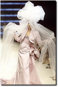 With a veil like this, it would be amazing if this woman didn't trip on it as she walks down the aisle. Anyway, still looks pretty ridiculous and more suited for mosquito bed netting.