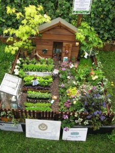 Now this is a lovely miniature garden with a shed, place for seedlings, and even a scarecrow. Yet, you can tell which side is for flowers and which is for vegetables.