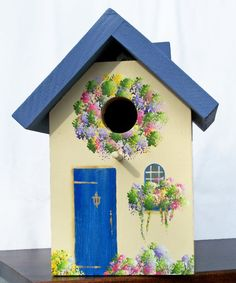 Now this is a lovely little birdhouse I wouldn't mind having in my yard. It seems so picturesque, especially the floral wreath around the hole.