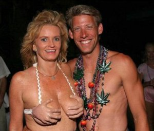 Oh, wait, that's her swimsuit top that resembles hands on her breasts. Also, the guy's wearing a necklace with pot leaves on it. Explains a lot about the woman's swimsuit is picture and the fact that both of them are totally high.