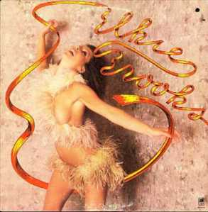 This was Elsie's idea for her album cover. She wanted to get closer to her roots while she was a struggling stripclub dancer at The Gaylord Club. She often wore the feather boa outfit in her act as well as danced with streamers.