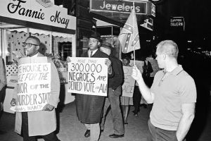"FILE - ""In this April 14, 1964 black-and-white file photo, a man holds a Confederate flag at right, as demonstrators, including one carrying a sign saying: ""More than 300,000 Negroes are Denied Vote in Ala"", demonstrate in front of an Indianapolis hotel where then-Alabama Governor George Wallace was staying."" The Confederate Flag enjoyed a resurgence of popularity after World War II, particularly to white supremacists who saw the rising Civil Rights Movement as a threat. Let's just say white segregationists' use of the Confederate Flag was no accident."