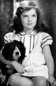When this little girl grows up, she's going marry John F. Kennedy and become one of the most iconic First Ladies in history. She'll also marry a Greek shipping tycoon later on as well. But now, she'd rather sit with her cute dog.