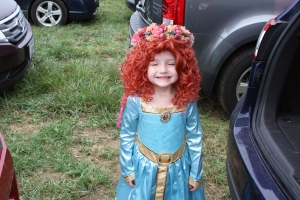 She's supposed to be Princess Merida from Brave. And she's so adorable and happy. However, I'm not sure if that's the costume Merida wore in the movie though.