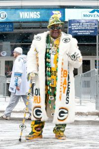Yes, he might be dressed like a pimp in his Green Bay Packers regalia. However, at least he's dressed for the weather because it's snowing in this picture.