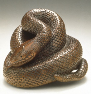 This is another old artwork from Japan. And it almost seems quite lifelike for a wooden snake. But it's curled in the shape of a turd.