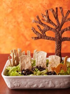 Now I'm sure the dip is under the olives and lettuce. Still, I have to admire how this person used the tortilla chips for the gravestones, tree, and cat.