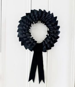 Now this wreath seems mostly laced with black streamers. Also, resembles a wreath you'd expect to see in a funeral home.