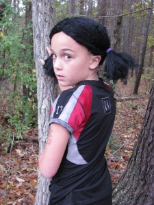 In the story, Rue is a tribute from District 11 who befriends Katniss. She's about 12. Still, she doesn't last.