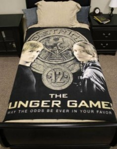 "From Zimbio: ""You'll sleep soundly every night knowing that Peeta and Katniss are there to protect you. This Hunger Games bedspread is also a total chick magnet, so... win/win."" I'm not so sure about that."