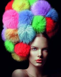 To me this either resembles a clown afro or her coiffe being taken over by rainbow tribbles. I'm not sure which is which.
