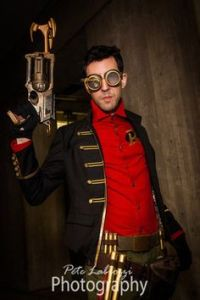 This is Steampunk Robin. While his modern counterpart wears a cape and tights, he goes with a red shirt, coat, and goggles.