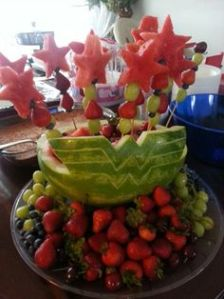 This watermelon is shaped like Wonder Woman's symbol. And many fruits are on skewers with watermelon stars.