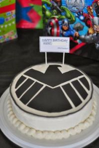 Now we know the kind of cake someone should get for Nick Fury's birthday party. After all, even though S.H.I.E.L.D. is a secret organization, its logo appears everywhere.