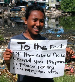 As sea levels rise, the existence of entire island nations are increasingly in jeopardy. This Pacific Islander is holding as sign asking the rest of the world to prepare a place where her country can stay. To some, climate change might mean losing a way of life or a home. To this girl, it means losing a country and everything with it.