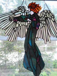 Must be a guardian angel motif. But this one has brilliant wings and an iridescent gown.