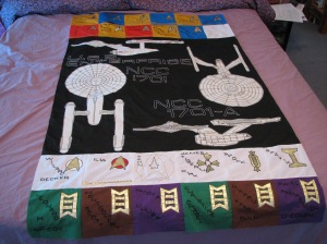 As you see, this quilt depicts the Enterprise from different views. Also, lists the main crew's names by rank.