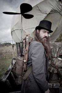 I don't think it will help him fly. But you have to like him in a bowler hat and a ZZTop beard.