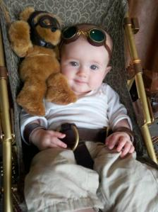 Yes, this is a baby in a steampunk costume which is so adorable. The teddy is even dressed up as well.