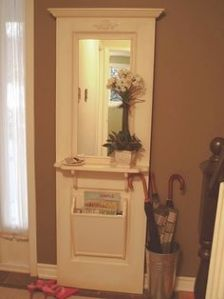 This includes a shelf, mirror, and mail bin. The flowers add a decorative touch.