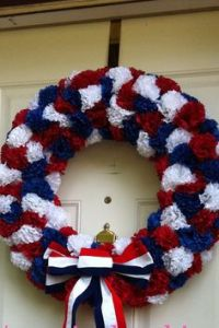 Yes, this is another flower 4th of July wreath. But this one has the flowers closer together and a red, white, and blue ribbon in front of it.