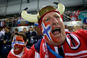 Sure his Viking ancestors didn't wear horned helmets in battle. But he doesn't care. He and his buddy also have their faces painted in the Norwegian flag.