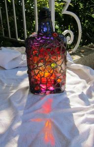 Now this bottle mosaic has to be made from stained glass. Yet, uses a sunset color scheme.
