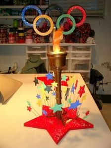 Features Olympic rings and a light up torch. Also has stars on the bottom. Love it.