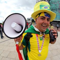 Because he's carrying a megaphone with him. Doesn't hurt he's clothed in Brazilian attire.