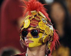 Because he has a hat with a lot of USC pins on it. And you can barely see the hat other than the plume on top.