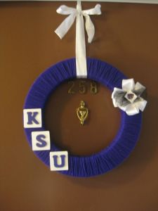 This purple yarn wreath only has KSU, a white flower, and a white ribbon. But it looks charming just the same.