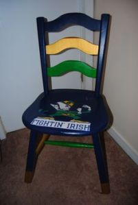 This is a wooden chair painted with Notre Dame colors. And yes, the Fightin' Leprechaun is in the seat.
