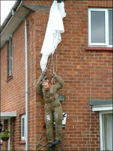Now he's hanging from the roof in his parachute. Must be WWII blitz inspired.